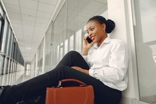 Smiling black woman talking on smartphone sitting on floor in corridor