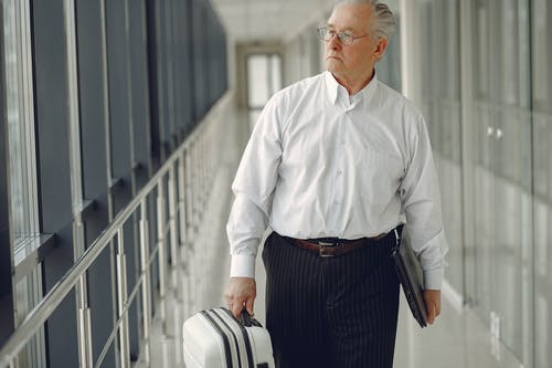 Serious senior male in formal clothes walking along airport corridor with baggage and laptop while looking away through window