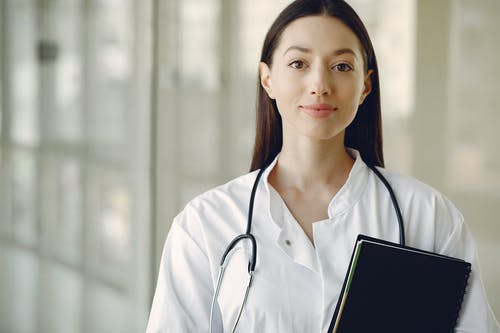 Crop smiling young ethnic female doctor in medical uniform with stethoscope and notebook standing in modern medical room with panoramic window