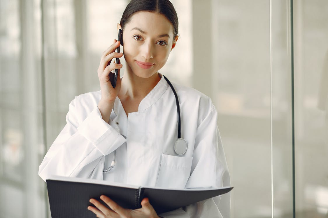 Positive doctor in medical uniform talking on cellphone in clinic corridor