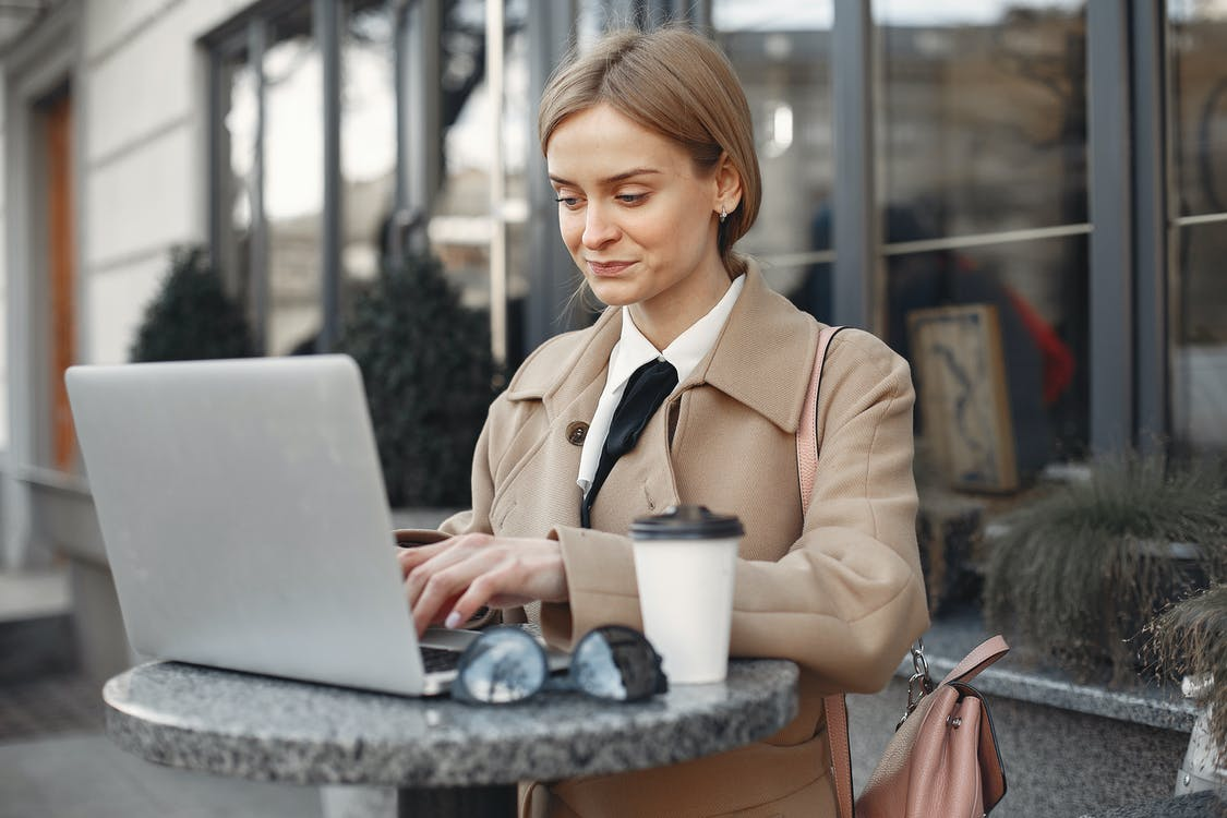 Focused businesswoman using laptop on high table of street cafe
