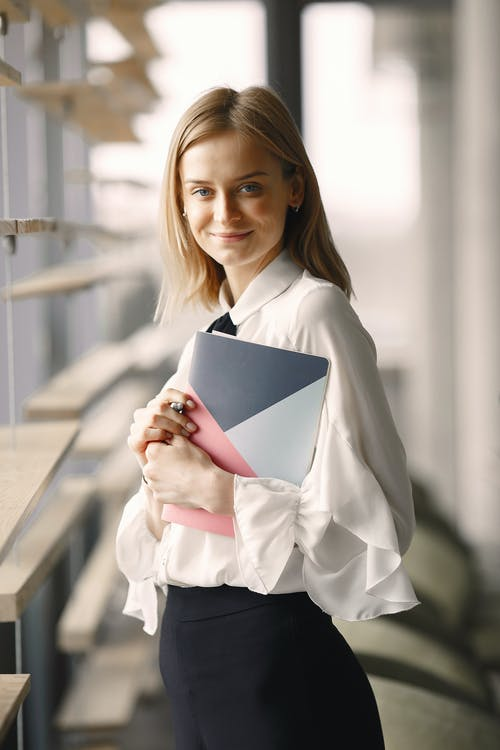 Positive employee in classy formal clothes standing with notebook near window in contemporary office hall