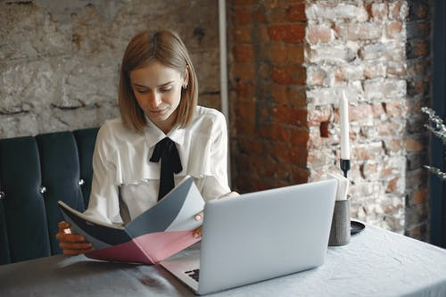 Focused businesswoman reading notes in planner in cafe