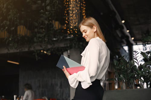 Smiling businesswoman reading notes in planner in cafe