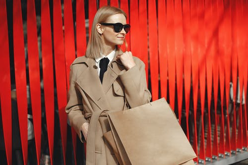 Stylish female in trendy coat and sunglasses standing with paper bags near red vertical jalousie