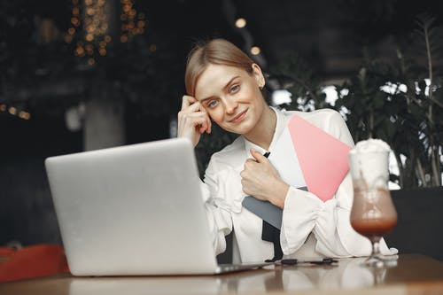 From below of smiling businesswoman in elegant clothes with notebook sitting at restaurant table with glass of Frappuccino and using laptop