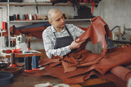 Focused adult male artisan in workwear and apron sitting in workshop among threads and cloths and sewing machines while checking leather material for quality