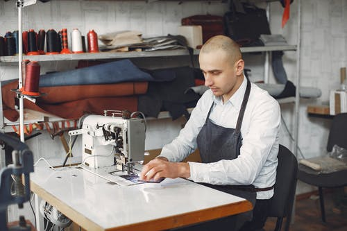 Concentrated artisan working on sewing machine in workshop