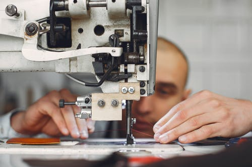 Unrecognizable artisan using sewing machine for sewing on leather fabric piece while creating handmade details in workshop