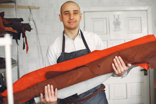 Positive male artisan with cloth rolls in studio