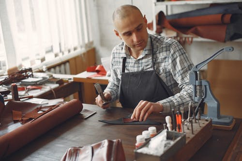 Concentrated adult male artisan in casual shirt and apron using leather piece and hammer while working in workshop
