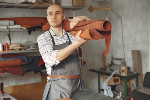 Serious focused craftsman in apron and gray check shirt standing with brown leather roll on shoulder while working in professional workshop and looking away pensively