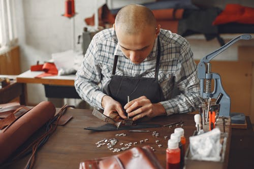 Artisan attaching metal snaps on leather