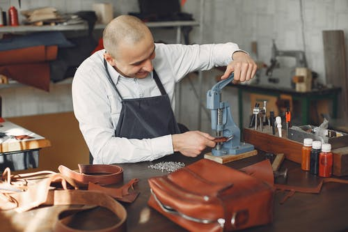 Cheerful craftsman attaching metal snaps on leather strip