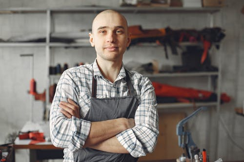 Positive young artisan in check shirt and apron standing with arms folded and looking at camera in contemporary workshop in daylight