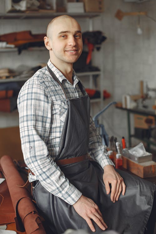 Happy young craftsman in plaid shirt and apron sitting on table in modern workshop and looking at camera in daylight