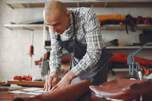 Concentrated artisan in plaid shirt and apron lining piece of leather with ruler and marker while working in professional workshop