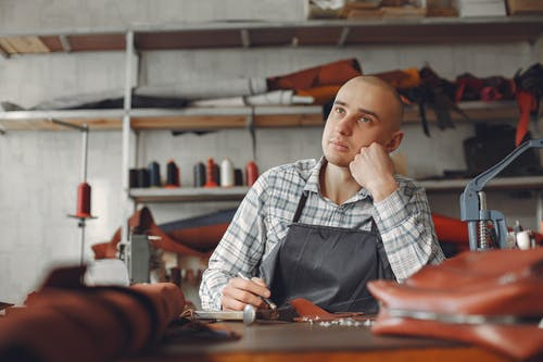 Positive young craftsman in check shirt and apron sitting at table in professional workshop and thinking about creating new design while leaning on hand