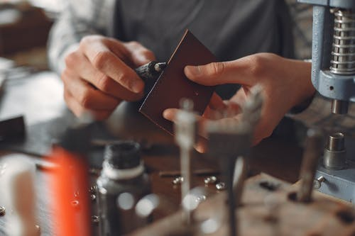 Crop artisan polishing leather edge in studio