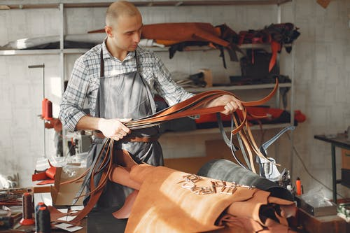 Focused young man making belts in workshop