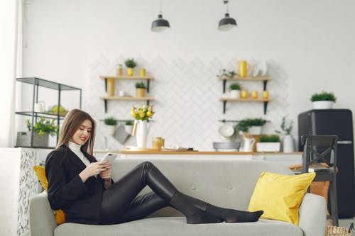 Young woman messaging on smartphone in living room