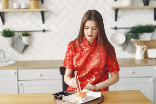 Focused young woman using chopsticks for sushi in kitchen