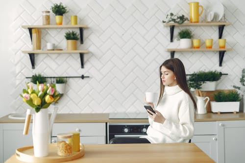 Side view of focused young woman in warm sweater browsing mobile phone in cozy kitchen and drinking hot beverage while resting at table with bouquet of tulips in kitchen