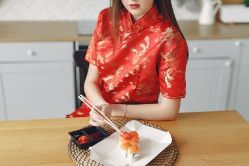 Crop female eating sushi in modern kitchen