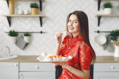Happy young female with long dark hair in vivid dress enjoying Japanese traditional cuisine and eating appetizing sushi while having lunch in modern light kitchen