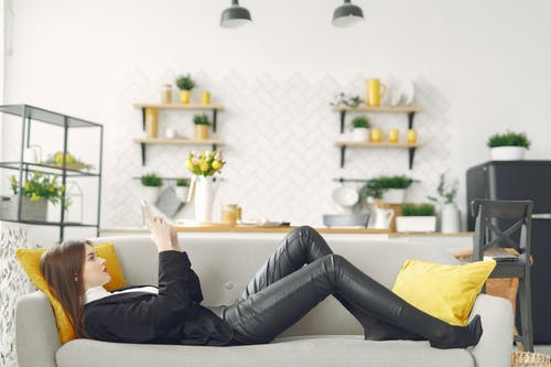 Young woman with smartphone lying on sofa in living room