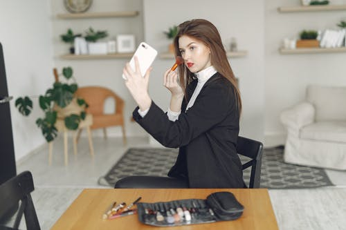 Young female blogger recording video on smartphone at home