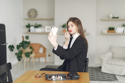 Young lady having video call on smartphone at home
