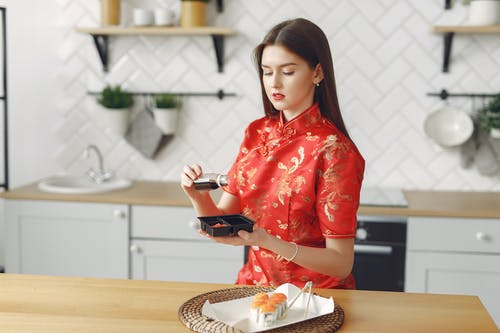 Focused young woman in stylish vivid dress having lunch and eating takeaway sushi while sitting in cozy light kitchen during daytime