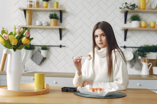 Young female eating sushi in modern kitchen