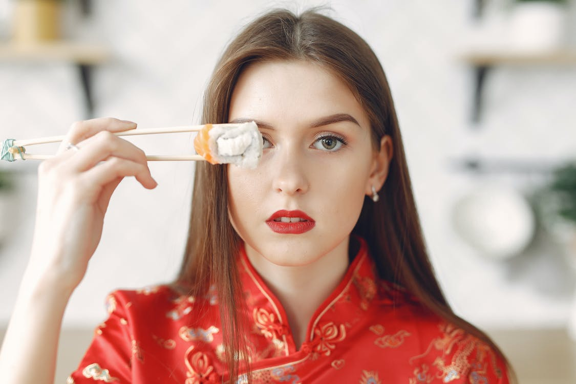 Young lady with dark hair in stylish wear holding chopsticks with sushi and covering eye while resting in light kitchen at home