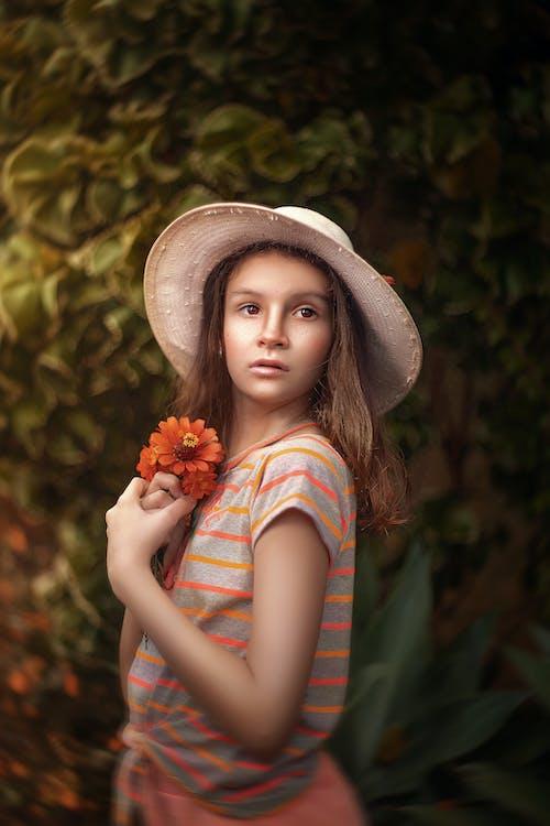 Girl in Orange and Blue Floral Shirt Holding Orange Flowers
