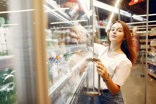 Happy young lady choosing cold beverages in grocery store