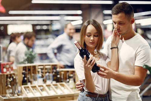 Young man and woman in casual outfit hugging and looking on bottle of wine while choosing alcohol for lunch in contemporary store together
