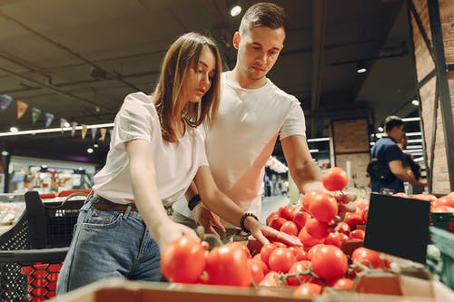 Happy couple choosing food in supermarket
