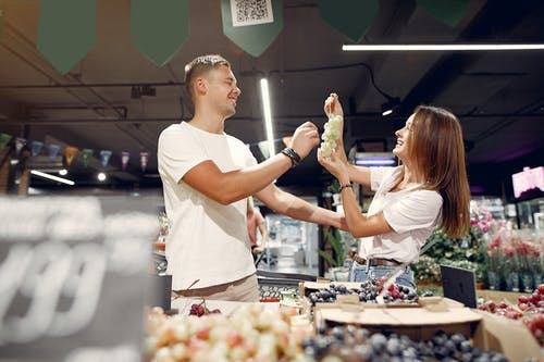 Side view of young man and woman in casual wear standing near counter and playing with each other while choosing grape in supermarket
