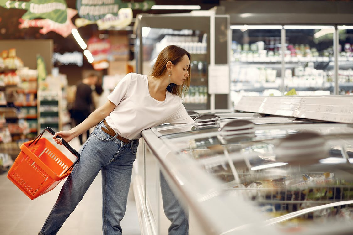 Focused young woman in casual wear picking food from showcase fridge and holding grocery basket while buying products in modern supermarket