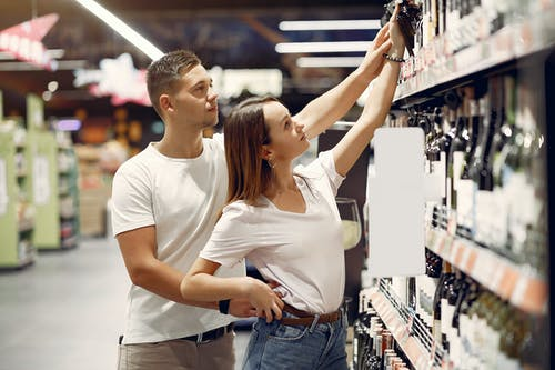 Young couple choosing food in grocery store
