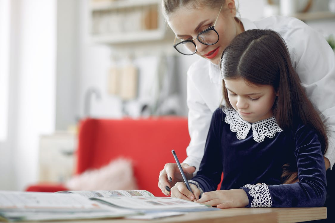 Young girl in casual clothes sitting at table and writing with tutor while working on homework assignment together in contemporary apartment