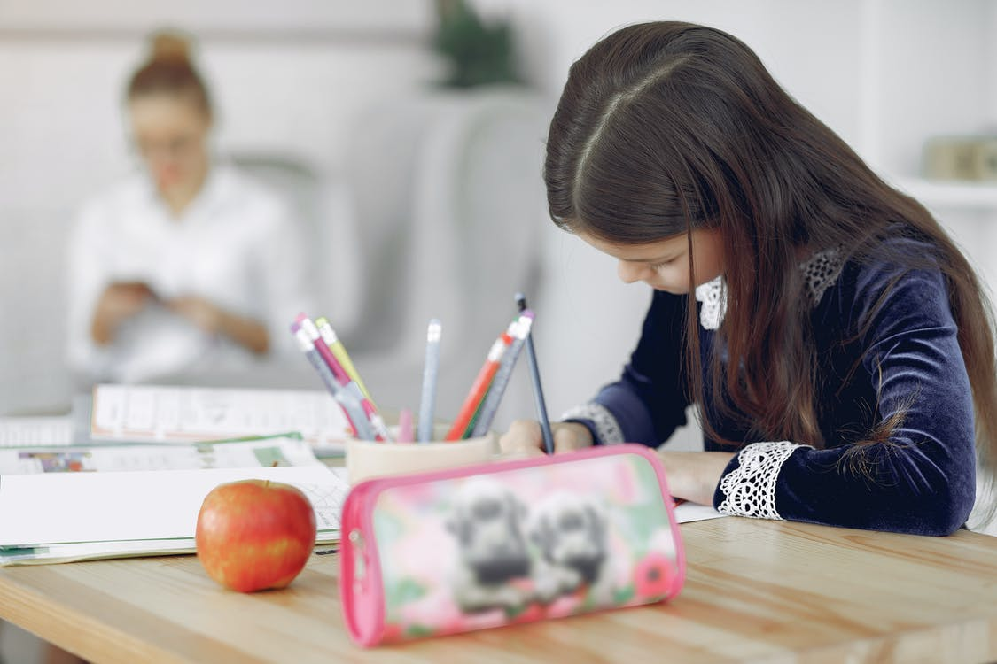 Focused young girl in school uniform sitting at table with stationery and apple while writing in copybook during studies against mother in modern apartment