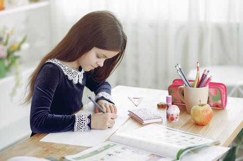 Side view of concentrated little girl sitting at wooden table at home and doing homework assignment while writing in notebook