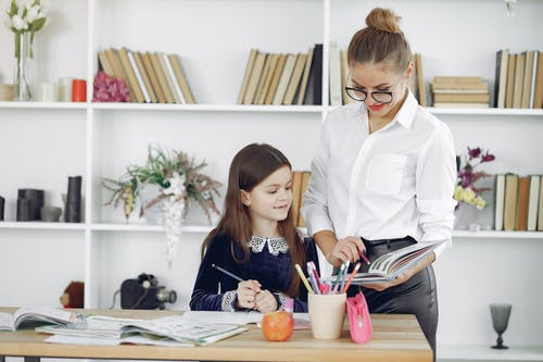 Thoughtful teacher and schoolgirl doing homework