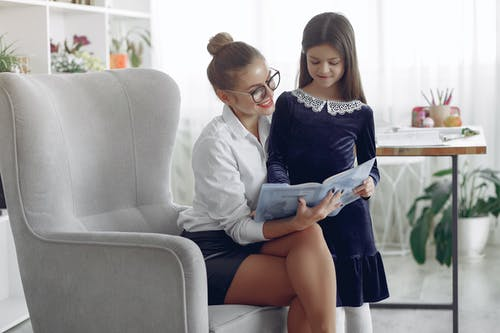 Positive female in formal wear and eyeglasses sitting in armchair at home and doing homework task with schoolgirl in dress