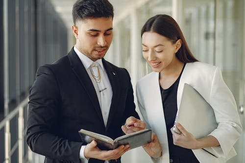Focused diverse coworkers in formal clothes with notebook and laptop in hands standing in hall and discussing business project together