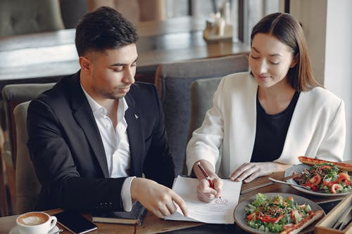 Concentrated multiethnic colleagues in formal clothes sitting at table in cafe with cup of espresso and plates of salad while signing documents