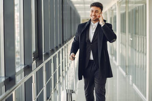Happy ethnic male in formal suit standing in modern hallway while holding suitcase in hand and talking on mobile phone